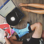 Load image into Gallery viewer, man and women sitting with record player and blue patterned socks