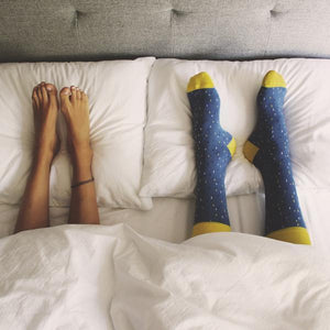 patterned socks in bedroom with man and woman on duvet