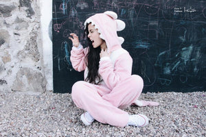 girl outside wearing pink dinosaur adults onesie