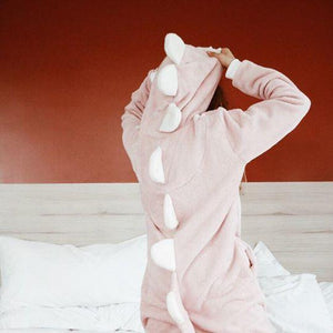 women's dinosaur onesie worn by model in bedroom
