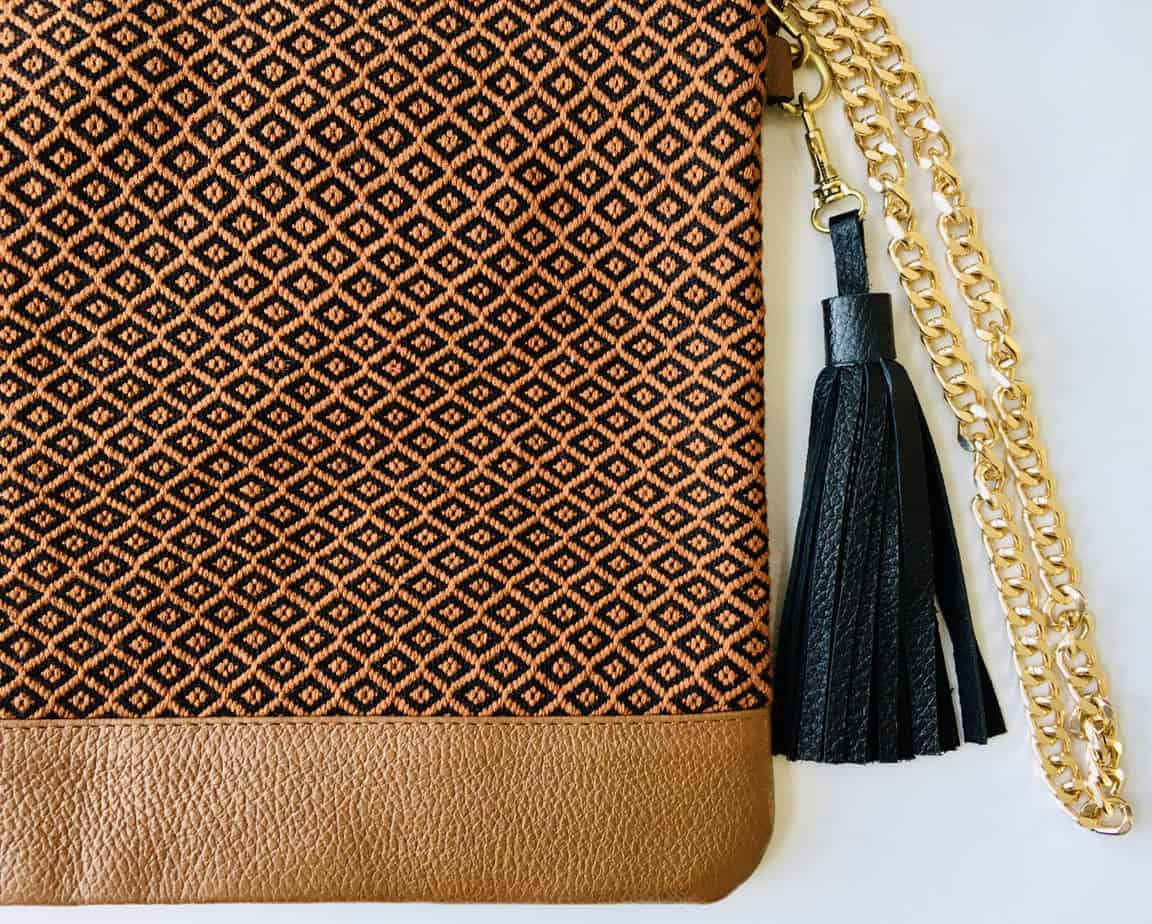 brown artisan bag with handmade textile detailing, gold chain and black tassle