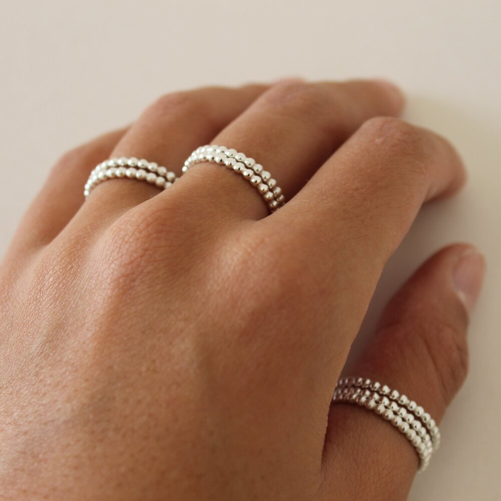 Women's silver rings on index finger and thumb