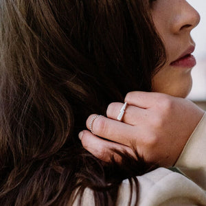 Woman with dark hair wearing silver rings
