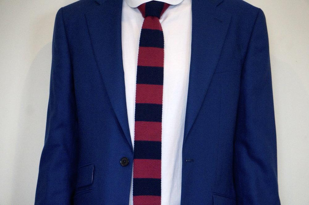 woven red and navy tie modelled on white shirt and with blue suit