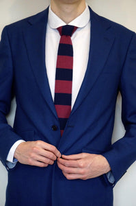 model buttoning up blue suit with red and navy tie