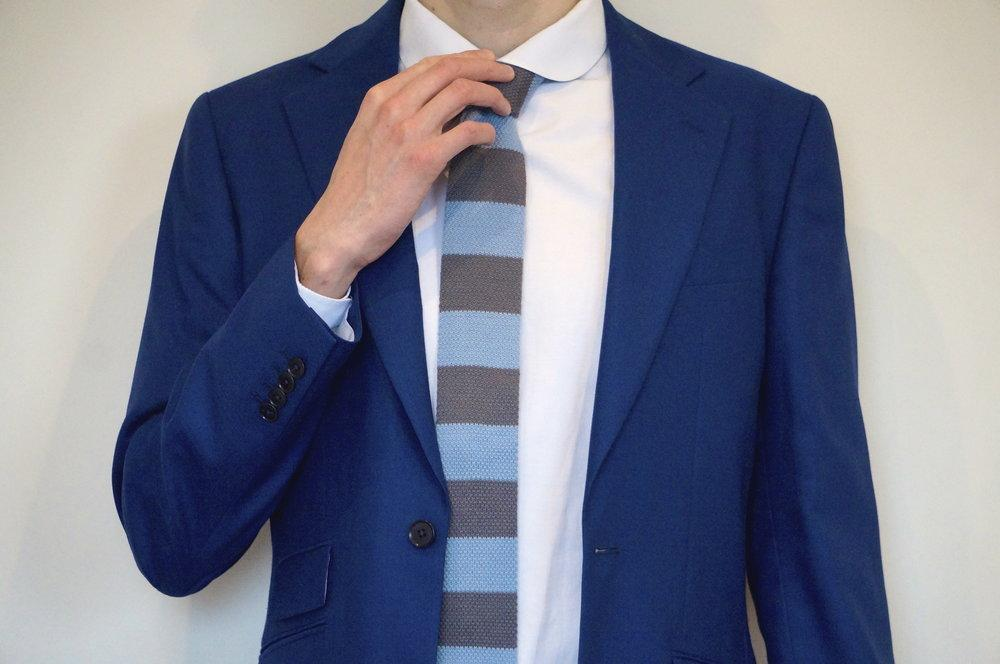 man in blue suit and white shirt wearing striped grey woven tie