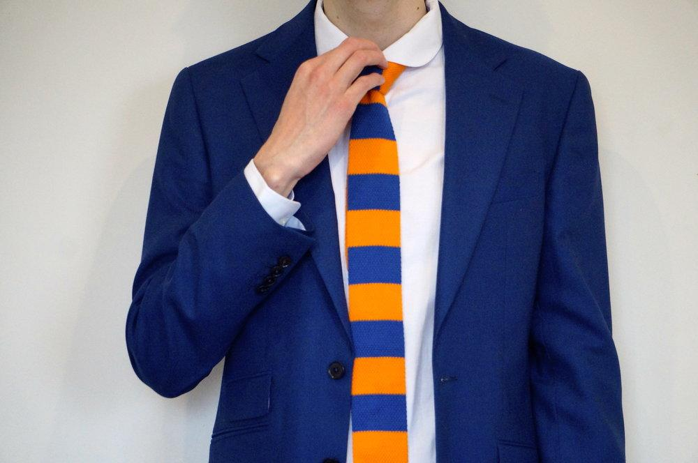 model wearing blue suit with skinny yellow and blue striped tie