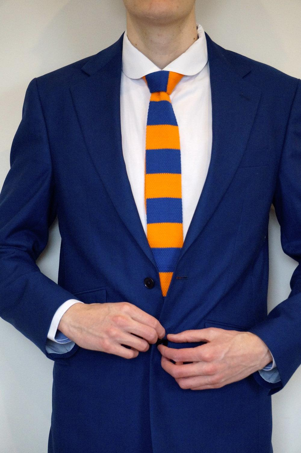 model wears blue suit with white shirt and blue and yellow rugby tie