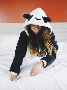 black and white panda onesie on bed