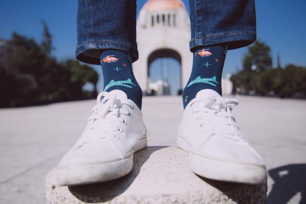 blue mens socks with white shoes in city background