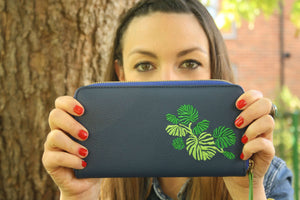 woman holding blue leather purse with green leaf embroidery