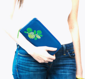 woman wearing white top and blue jeans carrying blue leather purse with green embroidered pattern