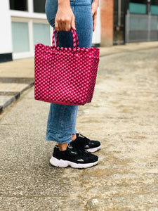 Pink woven Mexican handbag with handles in street