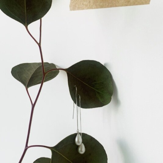 silver pearl earrings hanging from leaves