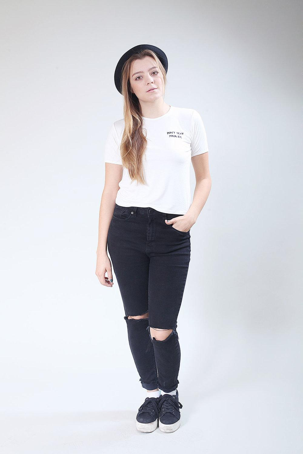 girl wearing jeans and white slogan t-shirt