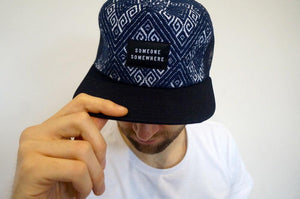 model wearing blue tucker cap with someone somewhere logo
