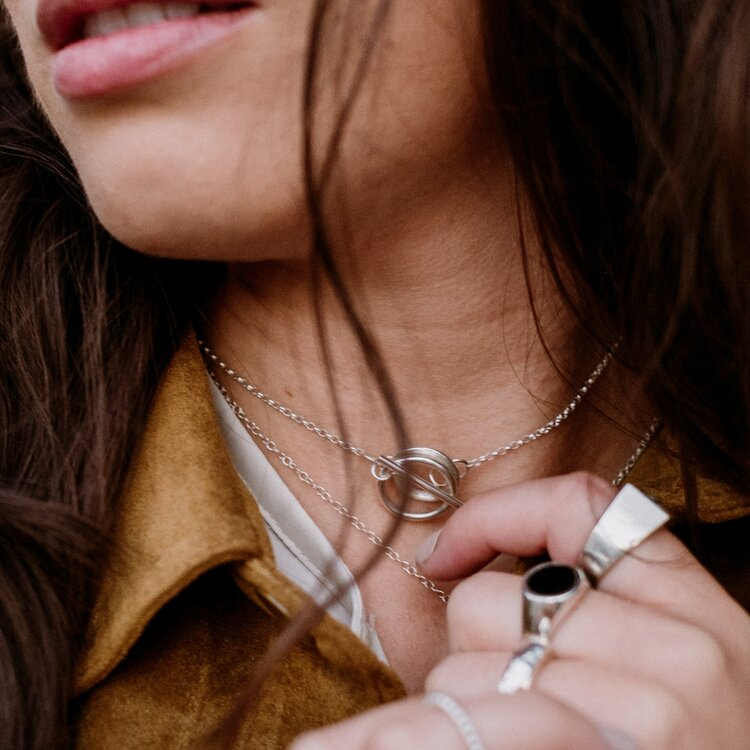 Circular silver toggle necklace worn by model