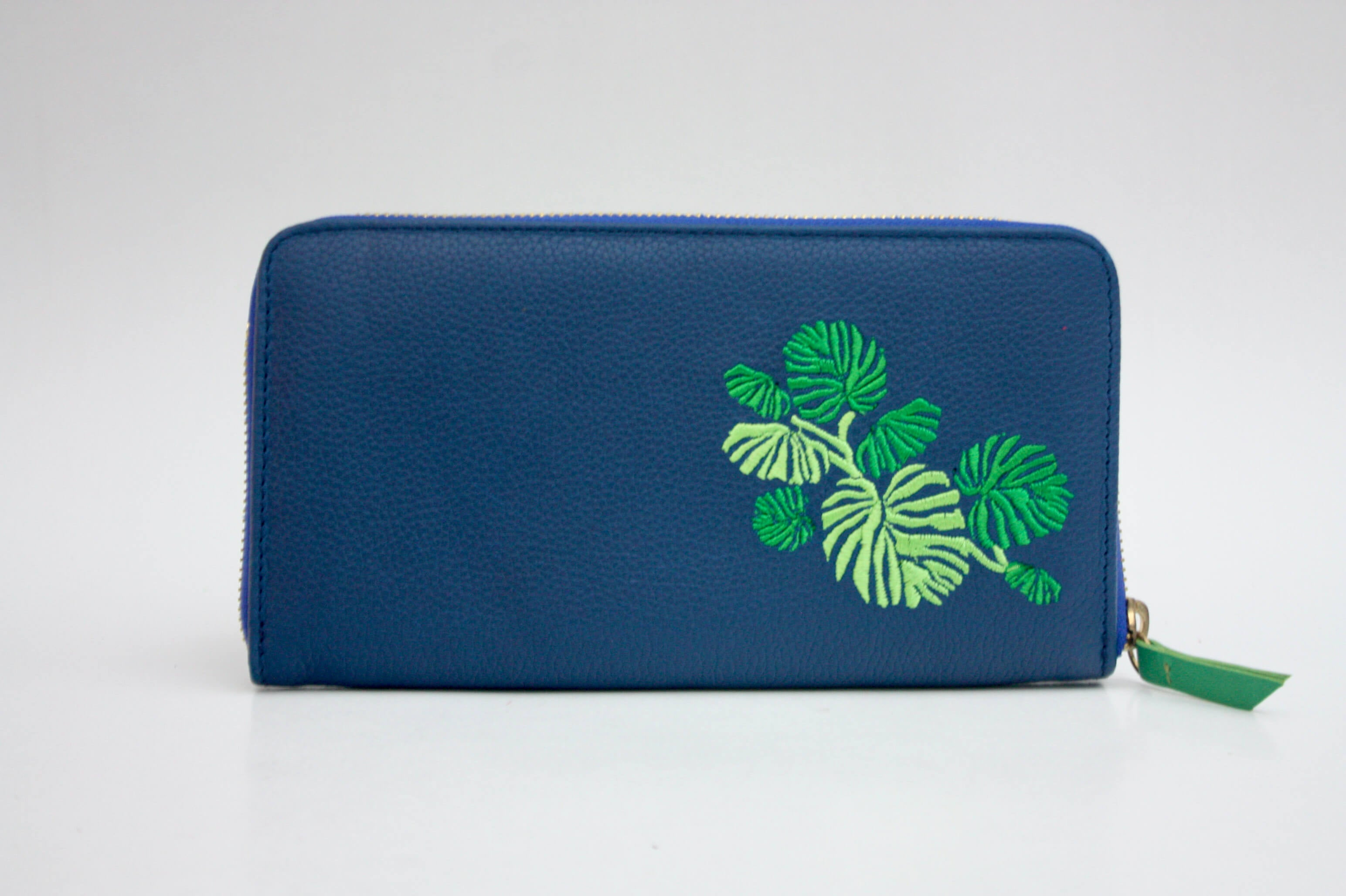 blue leather purse with green leaf embroidery
