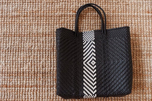 Black and white woven bag on a beige background