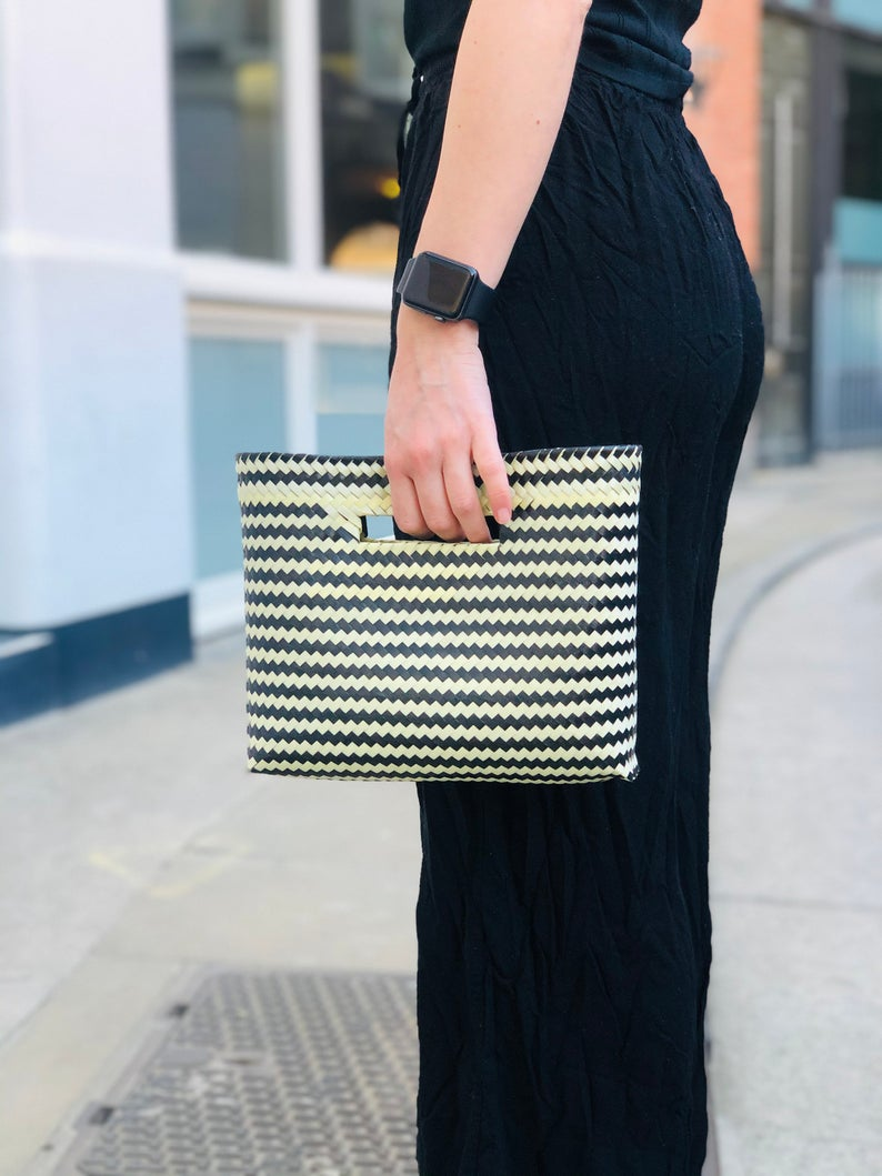 Women holding Mexican black clutch bag