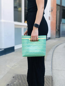 woman holding green Mexican clutch bag