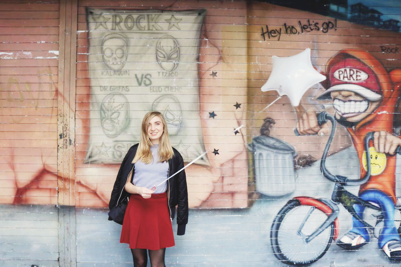 Girl in front of street art with balloon