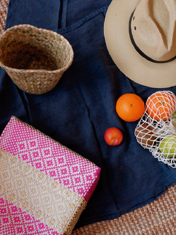 Woven bag, basket and hat with fruit on a picnic blanket