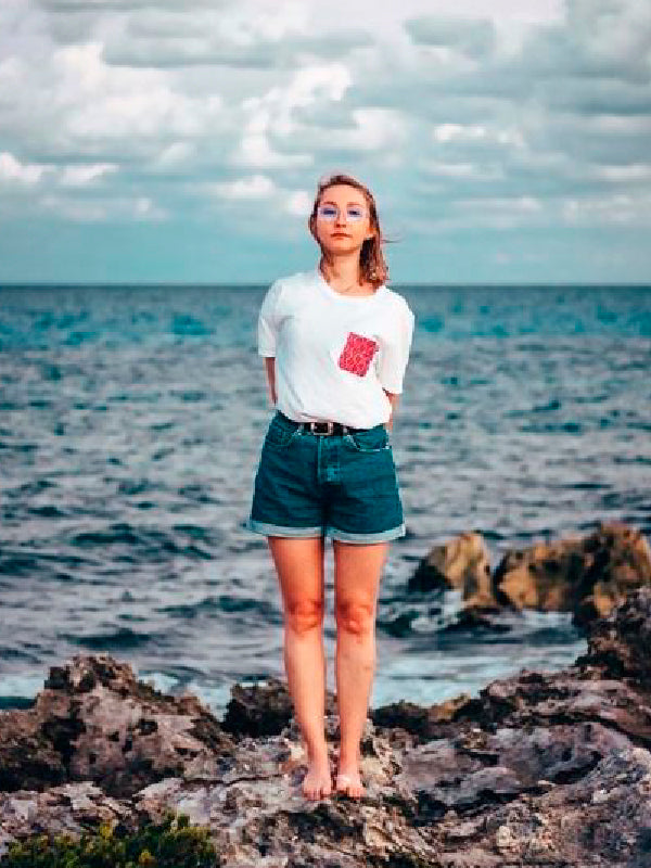 Woman wearing red pocket t-shirt by the sea