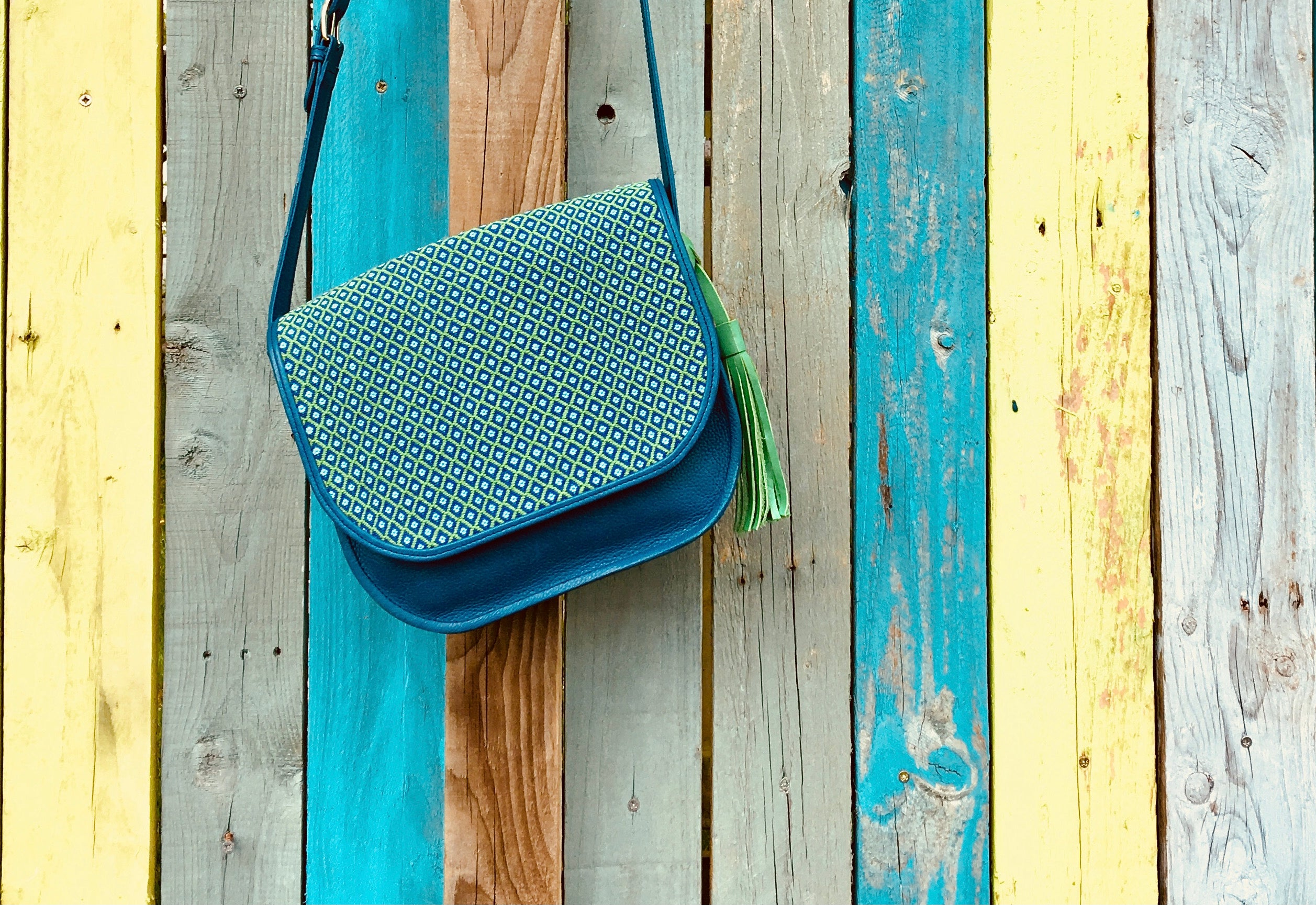 Blue embroidered leather bag hanging by strap from colourful fence