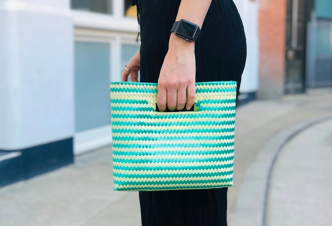 Woman holds a hand woven clutch bag