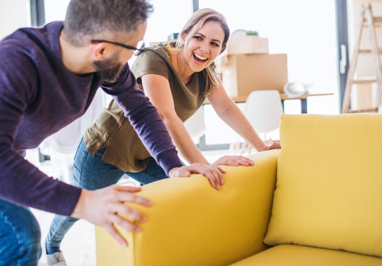 A young couple sliding a couch together