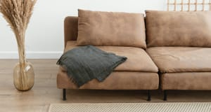 Leather couch with metal legs on hard wood floors