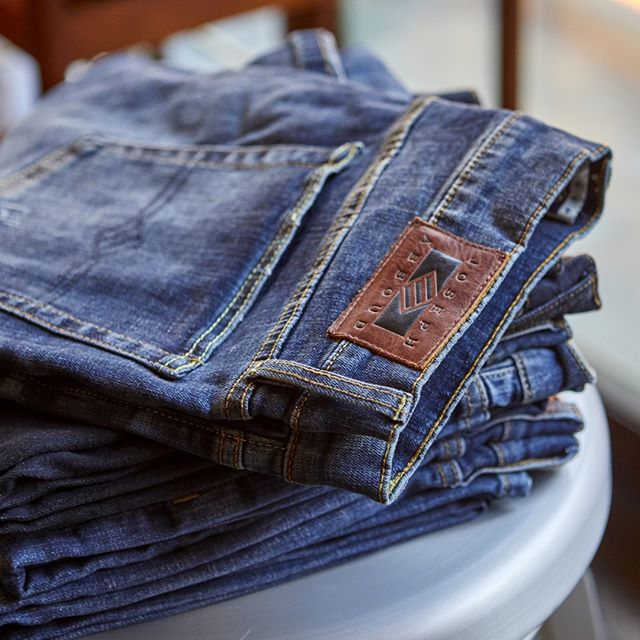 Several pairs of jeans on a table