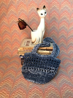 Aleksandra McCormack handmade crochet market bag dark blue navy melange space dye speckle tie dye white ivory hand made mini tote bag 100% cotton yarn french market bag farmers market bag design crochet mesh market bag filet market bag everlane filt french farmet bag cotton market bag small business new york city manhattan washinton heights flat view image with cat planter and rose arrangement