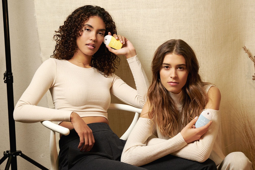 two models holding adrop hydrating sanitizer in hands blue and yellow