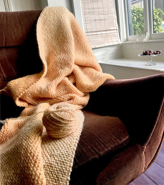 Hand knitted rose hip dyed woollen blanket on a G-Plan brown chair