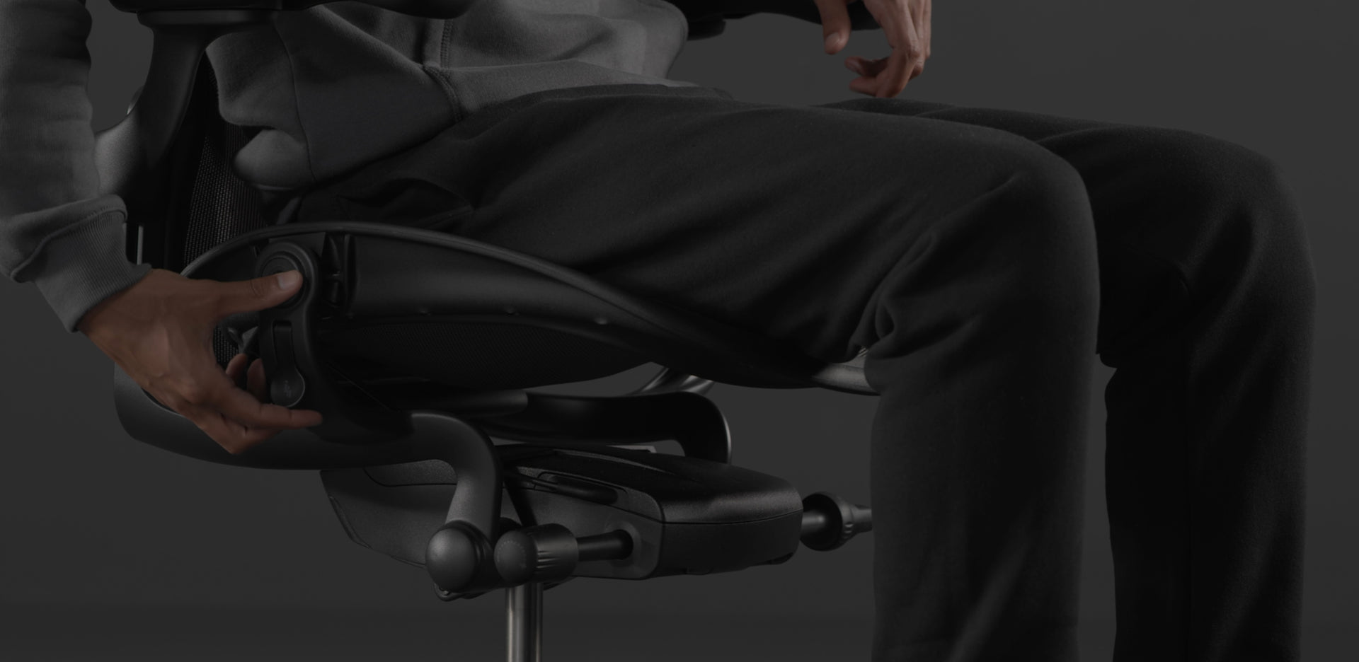 A close-up video of the side of a black Embody Gaming Chair adjustable seat depth mechanism being adjusted by a person in a sweater and trousers.
