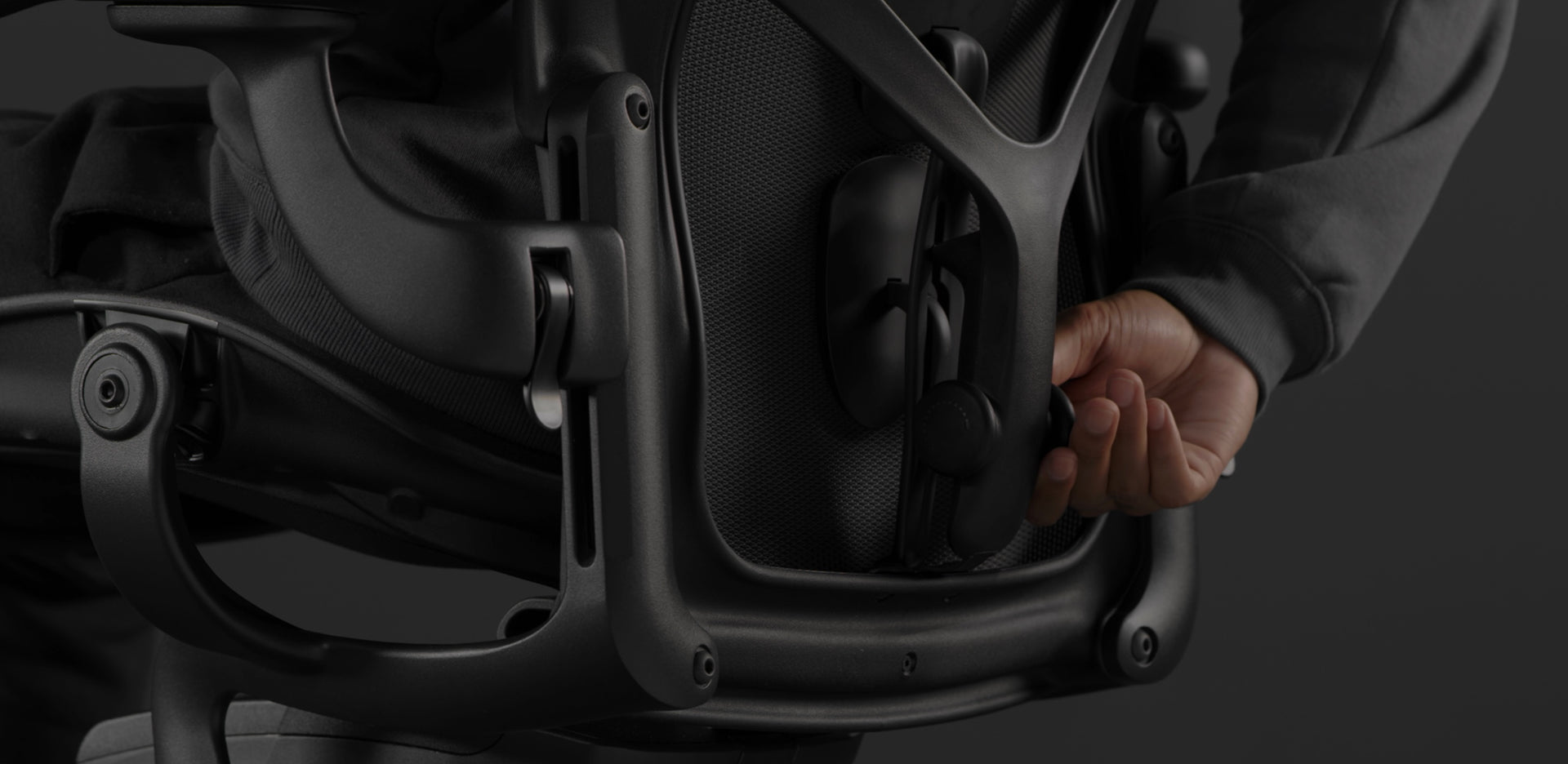 A close-up video of a black Embody Gaming Chair arm being adjusted by a person in front of a desk.