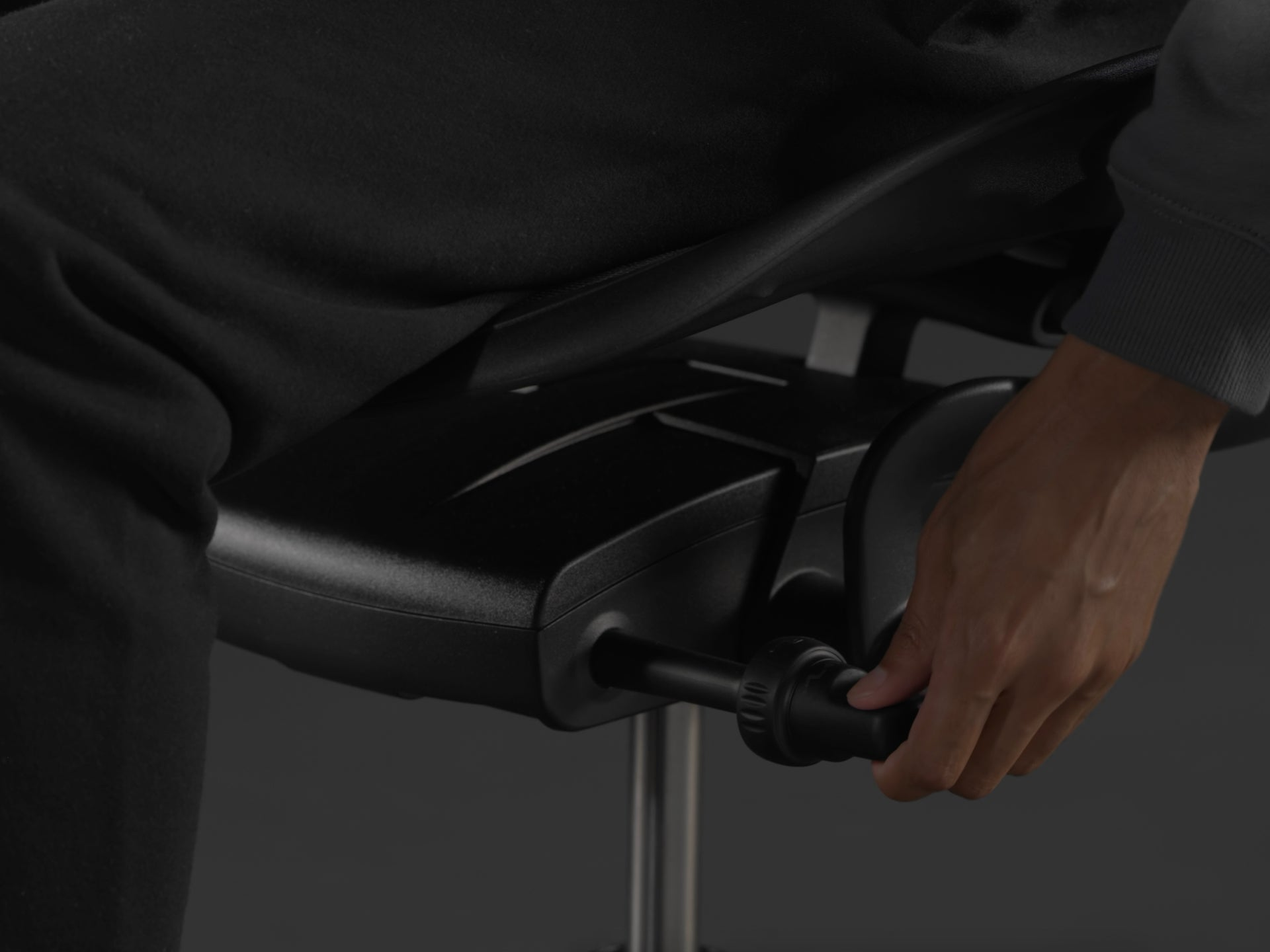 A close-up image of the side of the Embody Gaming Chair with a person adjusting seat height mechanism.