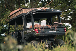 Lower rear full view of UTV featuring Swamp Ox roof rack in outdoor setting during the day. Black textured powder-coated hood and bed racks carrying outdoor gear and duck hunting equipment. Includes light package, unlit.