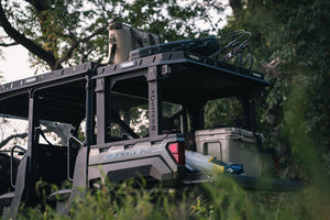 Lower side view of UTV featuring Swamp Ox roof and bed rack in outdoor setting during the day. Black textured powder-coated hood rack carrying outdoor gear and duck hunting equipment. Includes light package, unlit.