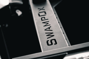 Closeup of SwampOx logo cut out of aluminum rack material.