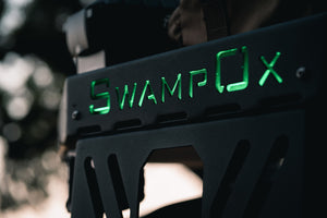 Closeup of Swamp Ox green lit-logo on front hood rack.