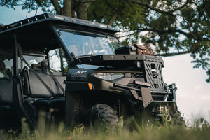 Angled front view of UTV featuring Swamp Ox hood rack, roof rack, and bed racks in grassy outdoor field. Black textured powder-coated racks all carrying outdoor gear.