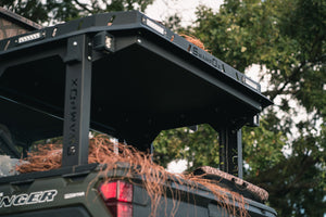 Angled closeup rear view of UTV featuring Swamp Ox roof rack in outdoor setting during the day. Black textured powder-coated hood rack carrying outdoor gear. Includes light package, unlit.