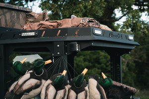 Upper closeup side view of UTV featuring Swamp Ox bed and roof racks in outdoor setting during the day. Black textured powder-coated hood rack carrying outdoor gear and duck hunting equipment. Includes light package, unlit.