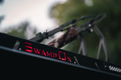 Closeup from below of red backlit Swamp Ox logo on roof rack.