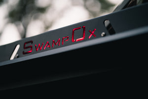 Closeup from lower right of red backlit Swamp Ox logo on roof rack.