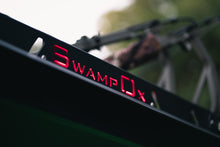 Load image into Gallery viewer, Closeup from lower left of red backlit Swamp Ox logo on roof rack.