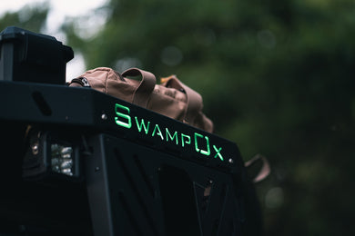 Closeup from below of green backlit Swamp Ox logo on front hood rack.